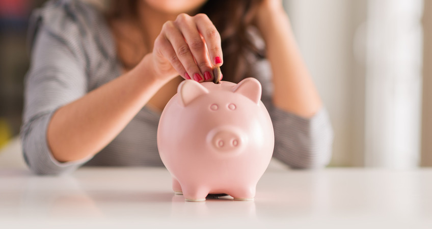 Woman Putting Coin In Piggy Bank, Indoors